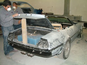 """Workers at Rainbow Collision Center in Volo, Ill., begin restoring the replica Ferrari Daytona Spyder that Don Johnson drove as Det. James Crockett during the first two seasons of the '80s television series """"Miami Vice."""" The Volo Auto Museum has acquired the car and plans to debut it during the upcoming holiday season. Volo Auto Museum is home to more than 300 collector and Hollywood cars and is open  seven days a week.  (PRNewsFoto/Volo Auto Museum)"""